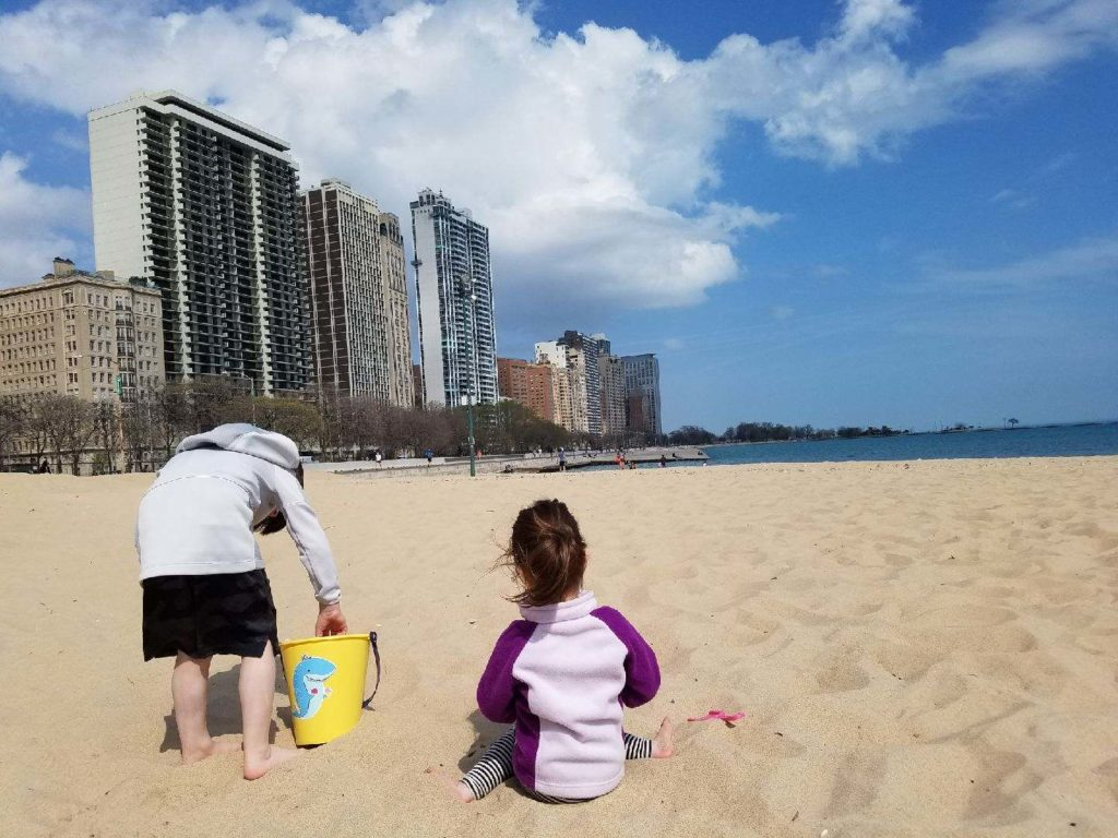 a kid and a toddler on the beach in Chicago